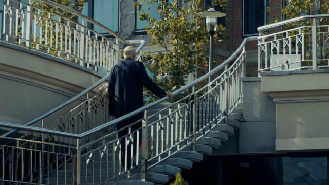 Senior man in suit walks upstairs to the urban building video