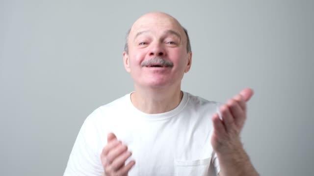 senior man in white t-shirt send air kissing. - maglietta bianca video stock e b–roll