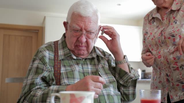 vídeos de stock, filmes e b-roll de homem sênior, inserindo o seu aparelho auditivo - surdo