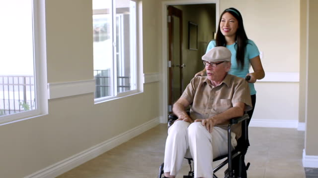 Senior Man is Pushed in Wheelchair by Young Asian Caregiver video