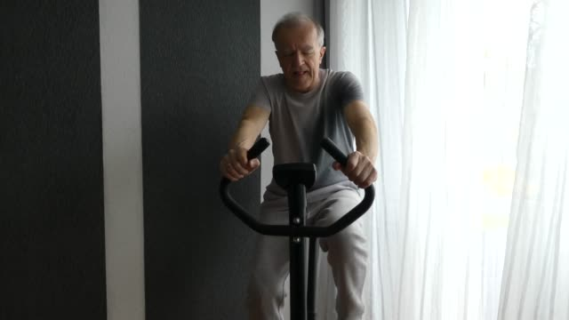 Senior Man is riding an exercise bike. Senior Man is exercising on stationary bike. exercise bike stock videos & royalty-free footage
