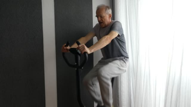 Senior Man is riding an exercise bike. Senior Man is exercising on stationary bike and ending his training with some stretching. exercise bike stock videos & royalty-free footage