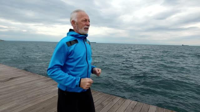 vídeos de stock, filmes e b-roll de senior man movimentando-se junto ao mar - persistência