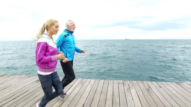 senior mannen jogging med ung kvinna intill havet - age bildbanksvideor och videomaterial från bakom kulisserna