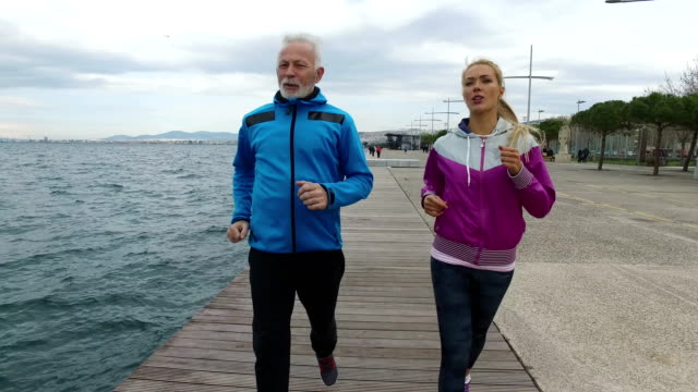 Senior man Jogging with young woman next to the sea Senior man Jogging with young woman next to the sea in Thessaloniki on the wooden Sea dock 50 54 years stock videos & royalty-free footage