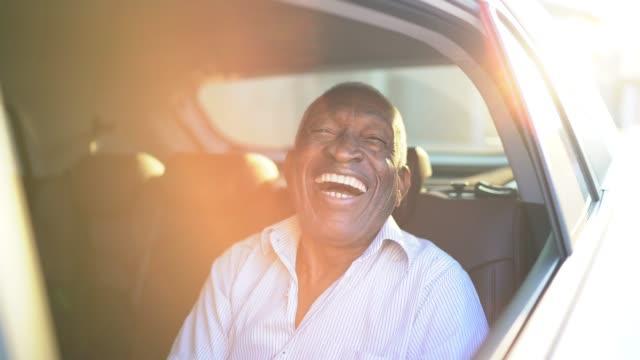 senior man laughing in the car - sorriso aperto video stock e b–roll