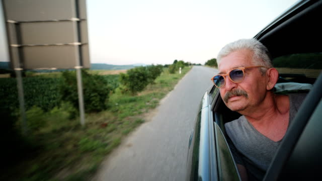 Senior man leaning out of a car window video