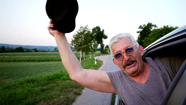 senior man leaning out of a car window - cappello video stock e b–roll