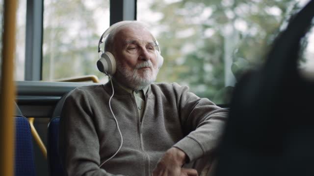 Senior man listening music on headphones in bus