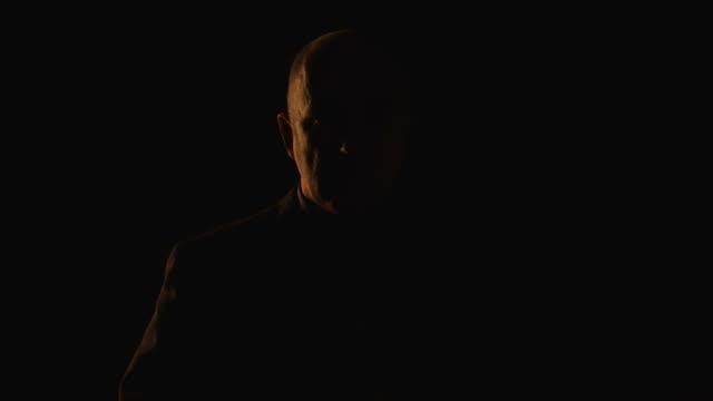 uomo anziano, guardando fotocamera - penombra video stock e b–roll