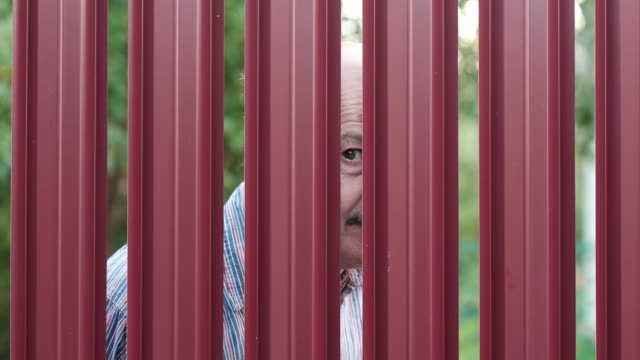 vídeos de stock e filmes b-roll de senior man looking through fence spying on his neighbor - cercado