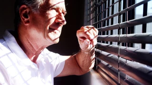 Senior man looking through window 4k video