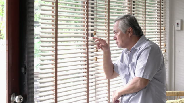 vídeos de stock e filmes b-roll de senior man looking to outside and miss somebody emotion at home.  concept of happy family, nursing home and quality of life. 4k resolution. - old men window
