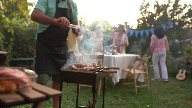 vídeos y material grabado en eventos de stock de hombre mayor haciendo barbacoa para sus amigos durante la fiesta en el patio trasero - grilling