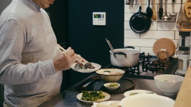 台所で東芝智彦年横断麺を作るシニアマン - 自家製点の映像素材/bロール