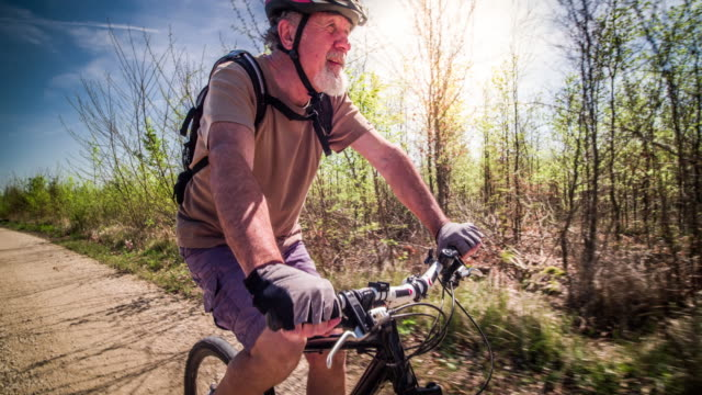 Senior Man Mountain Biking Senior man, 70 years old cycling in Germany. Back lit by warm sunlight with sun flare coming into the lens. He is wearing a cycling helmet. recreational pursuit stock videos & royalty-free footage