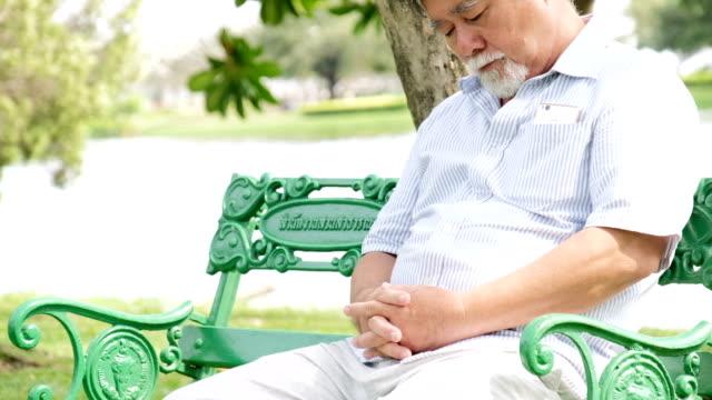 Senior man napping on bench video