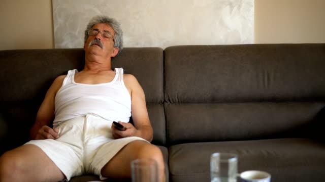 vídeos de stock e filmes b-roll de senior man napping on couch - sofá