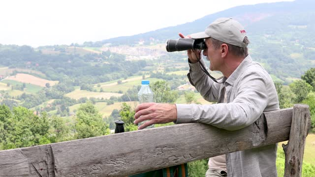 Senior man observing landscape via binoculars