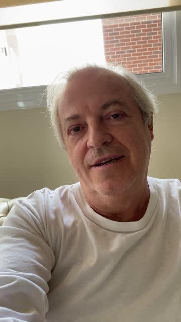 vidéos et rushes de homme aîné sur un appel vidéo à la maison - prise avec un appareil mobile