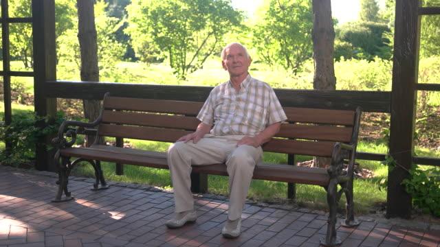 公園のベンチで年配の男性。 - ベンチ点の映像素材/bロール