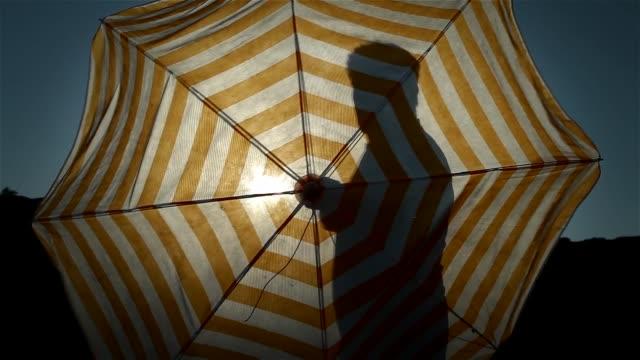 senior man öppnings parasoll på stranden. vyn bakgrundsbelysning. - brunbränd bildbanksvideor och videomaterial från bakom kulisserna
