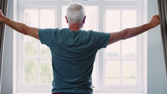 Senior Man Opens Curtains And Stretches In Front Of Window Senior Man Opens Curtains And Stretches In Front Of Window chance stock videos & royalty-free footage