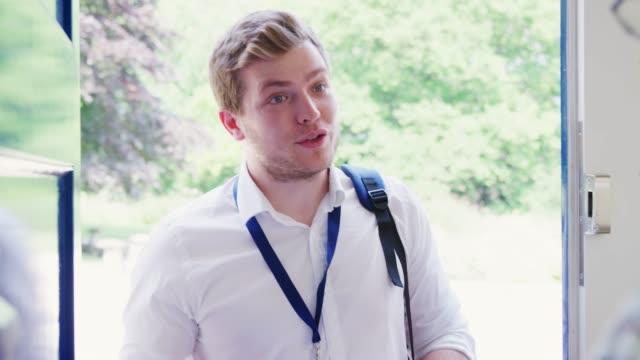 Senior man opens door to male charity worker doing survey