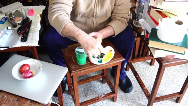 Senior man painting easter egg at Coronavirus quarantine