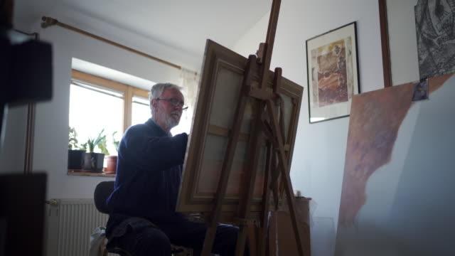 Senior man painting in his workshop