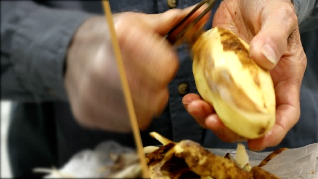 Senior man peeling fresh potatoes with a potato peeler. video