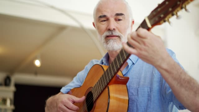 Senior man playing acoustic guitar