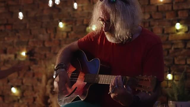 Senior man playing acoustic guitar video