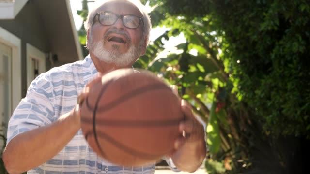 seniorenmann spielt basketball im freien - aktiver senior stock-videos und b-roll-filmmaterial
