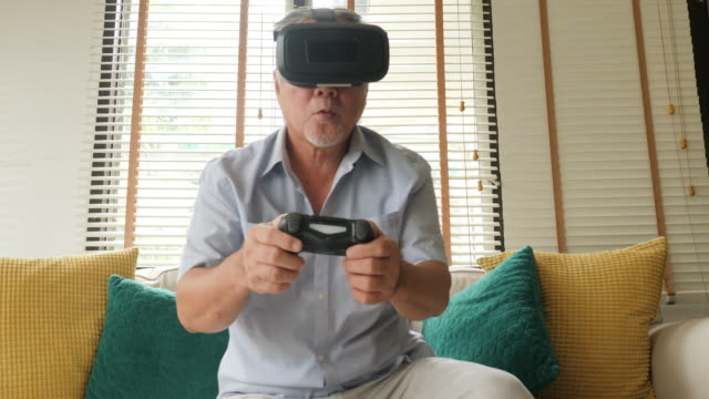 Senior man playing game at home with happy emotion. People with relaxation, old age, retirement, senior lifestyle concept.