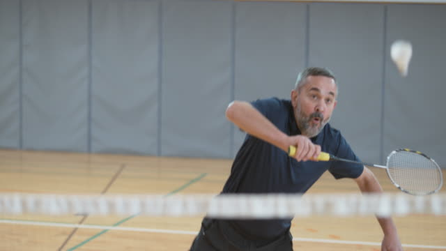 Senior man playing indoor badminton video