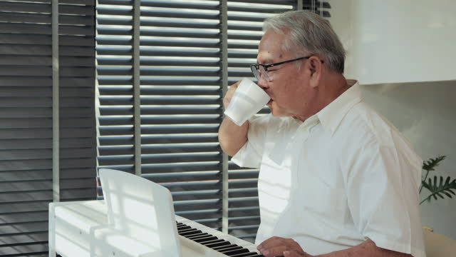 Senior man playing piano alone at home. He enjoying to play piano in living room.