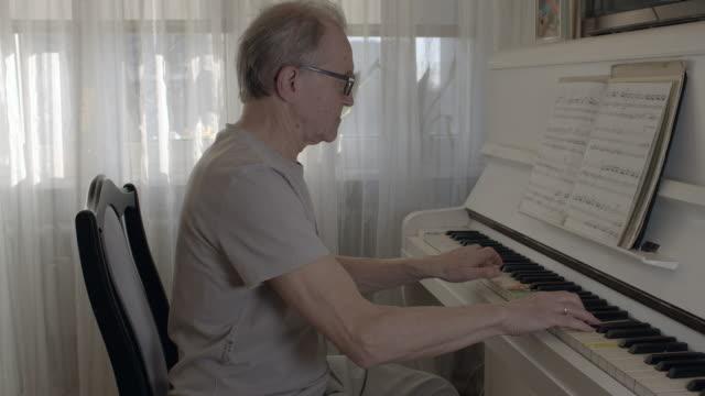 vídeos de stock e filmes b-roll de senior man playing the piano. - piano