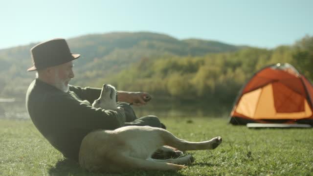 ältere mann spielt mit seinem hund am see - aktiver senior stock-videos und b-roll-filmmaterial