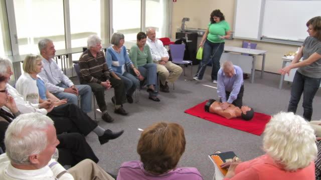 HD: Senior Man Practicing CPR On A Dummy