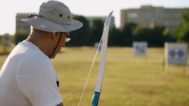 vidéos et rushes de homme aîné pratiquant le tir à l'arc dans le crépuscule - tir à l'arc