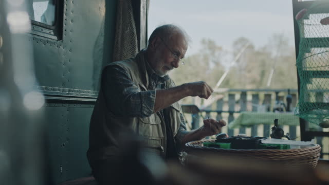 senior mann bereitet den köder zum angeln - angelhaken stock-videos und b-roll-filmmaterial