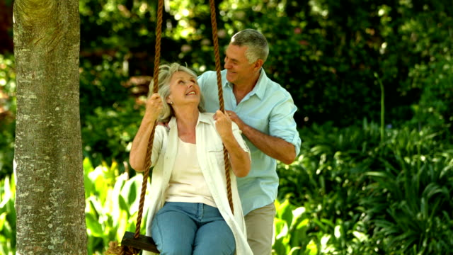 Senior man pushing his wife on a swing video
