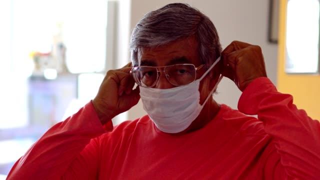 yüzüne koruyucu maske koyan kıdemli adam - maske stok videoları ve detay görüntü çekimi