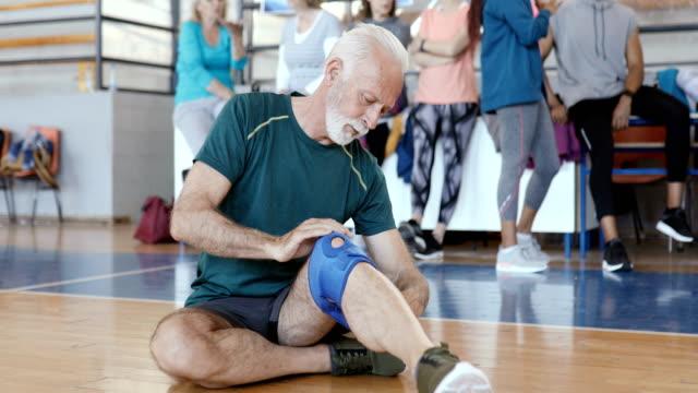 Senior man putting knee pad on his injured knee Senior man putting knee pad on his injured knee physical injury stock videos & royalty-free footage