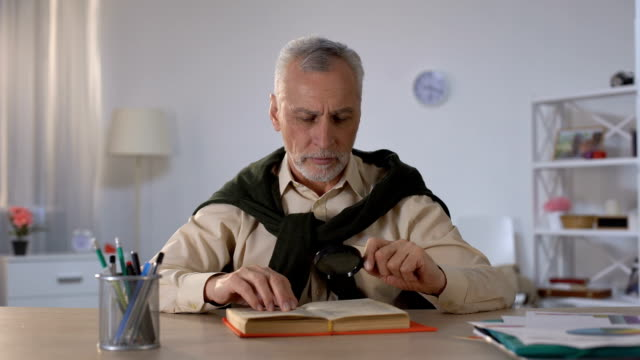 Senior man reading book with magnifying glass, attention to details, erudition