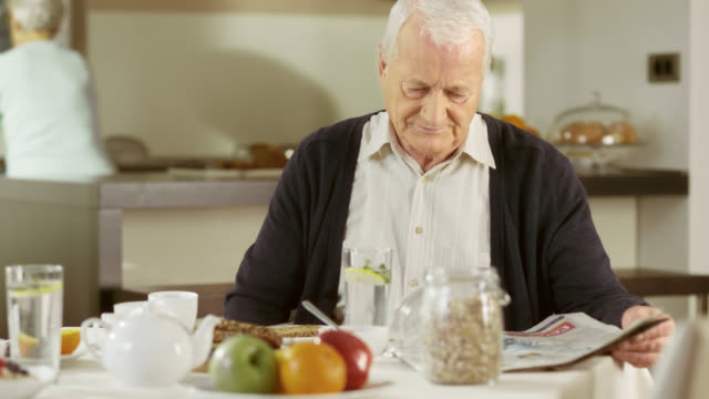Senior man reading his newspaper at breakfast table video