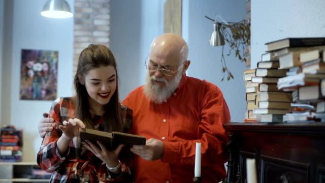stockvideo's en b-roll-footage met senior man leest boek samen met zijn prachtige kleindochter - literatuur