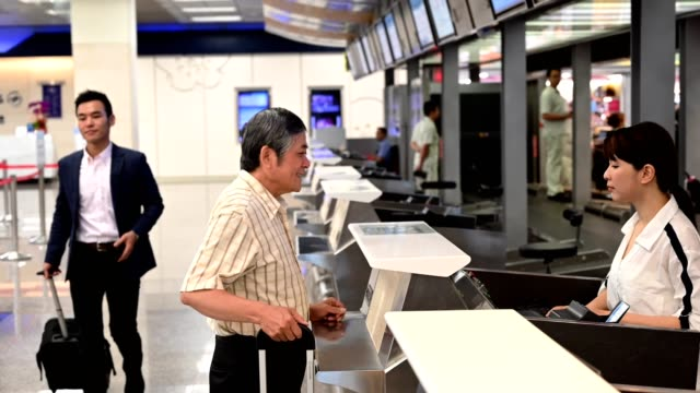 Senior man receiving boarding pass at counter