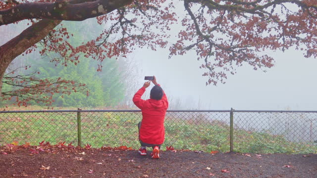 Senior man recording videos of autumn scene with a smartphone video